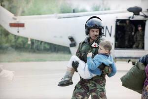 1993, Τούζλα.  Ένας Γάλλος πιλότος κρατάει ένα αγόρι που έχει μόλις φέρει στην Τούζλα από την πολιορκημένη πόλη της Σρεμπρένιτσα. Η Βρετανία ανακοίνωσε ότι τα αεροσκάφη της θα χτυπήσουν τους Σέρβυς εάν εκείνοι επιτεθούν στις δυνάμεις του ΟΗΕ.