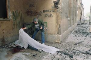 1992, Σαράγιεβο.  Ένας μουσουλμάνος πολιτοφύλακας καλύπτει ένα νεκρό σώμα. Οι συγκρουσεις στο κέντρο του Σαράγιεβο συνεχίζονται με σφοδρότητα.