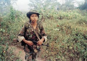 """1987, Νικαράγουα.  Ένα 14χρονο αγόρι ποζάρει με το όπλο του στη ζούγκλα της Νικαράγουα, λίγα χιλιόμετρα από τα σύνορα με την Ονδούρα. Είναι μέλος του στρατού που εισέβαλε στη Νικαράγουα από την Ονδούρα για να αντισταθεί στο κίνημα των Κόντρας. """"Πολεμάω ε"""