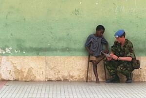 1995, Λουζάκα, Ζάμπια.  Ένας Βρετανός στρατιώτης μιλάει με ένα θύμα της πολιομυελίτιδας, έξω από το νοσοκομείο της πόλης του Λομπίτο. Ο εμφύλιος που σπαράσσει την περιοχή, κρατάει ήδη 20 χρόνια.