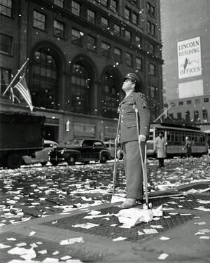 1945, Νέα Υόρκη.  Ο Λοχαγός Άρθουρ Μουρ, από το Μπάφαλο, ο οποίος τραυματίστηκε στο Βέλγιο, στέκεται στην 42η οδό, καθώς οι Νεοΰορκέζοι γιορτάζουν τη συνθηκολόγηση της Γερμανίας.