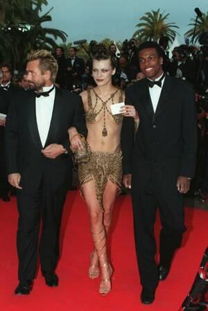"""1997, Κάννες.  Ο Γάλλος σκηνοθέτης Λικ Μπεσόν (αριστερά), φτάνει στο Φεστιβάλ Κινηματογράφου των Καννών με την Αμερικανίδα ηθοποιό Μίλα Γιόβοβιτς και τον Κρις Τάκερ. Η ταινία του Μπεσόν """"Το πέμπτο Στοιχείο"""" θα προβληθεί εκτός συναγωνισμού."""