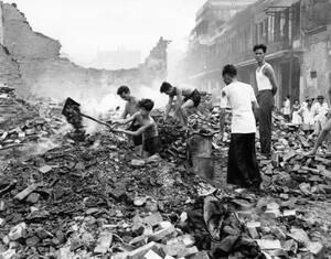 1955, Βιετνάμ. Διασώστες αναζητούν επιζώντες κάτω από τα ερείπια των σπιτιών στο Χολέν, το κινεζικό προάστιο της Σαϊγκόν στο Νότιο Βιετνάμ. Τα σπίτια καταστράφηκαν κατά τη διάρκεια αντεπίθεσης των Εθνικιστικών δυνάμεων εναντίον των ανταρτών.