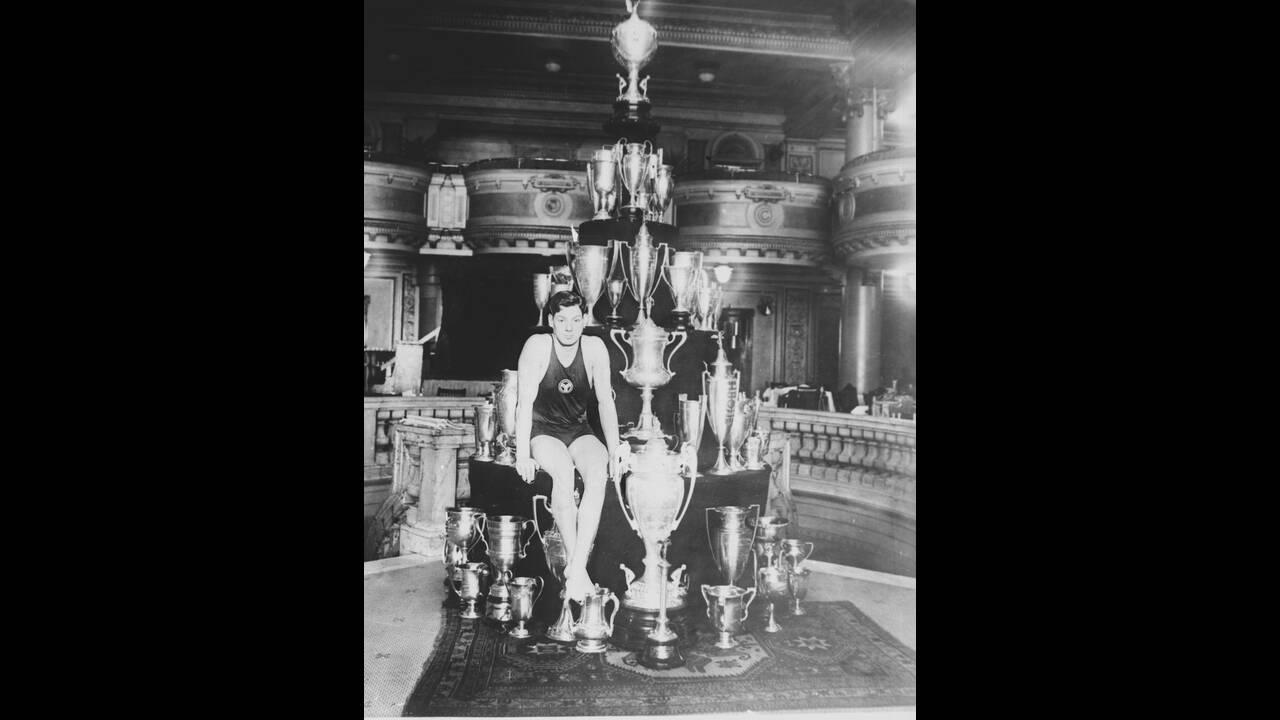 1927, Ιλινόις.  Ο κολυμβητής Τζόνι Βαισμίλερ -που αργότερα έπαιξε στον κινηματογράφο τον Ταρζάν- έχει καταρρίψει πολλά παγκόσμια ρεκόρ κι εδώ απεικονίζεται με μερικά από τα βραβεία του. Για μερικους θεωρείται ακόμα ο κορυφαίος κολυμβητής όλων των εποχών.