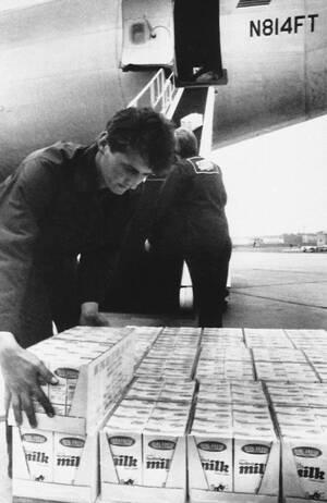 1986, Βαρσοβία.  Εργάτες ξεφορτώνουν γάλατα μακράς διαρκείας στο αεροδρόμιο Οκέντσε της Βαρσοβίας. Τα γάλατα έρχονται από την Αμερική για να βοηθήσουν τους Πολωνούς να αντιμετωπίσουν την κρίση τροφίλων που υπάρχει μετά την καταστροφή του Τσερνόμπιλ στη γ
