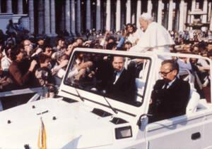 1981, Βατικανό.  Ο Πάπας Ιωάννης Παύλος ο Β' στην πλατεία του Αγίου Πέτρου χαιρετάει τα πλήθη. Στο άκρο αριστερά, πάνω από το κεφάλι του άντρα με τα γυαλιά ηλίου, διακρίνεται το όπλο με το οποίο πυροβολήθηκε λίγα δευτερόλετα αργότερα.