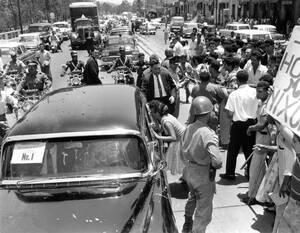 1958, Καράκας.  Κάτοικοι του Καράκας φωνάζουν και διαμαρτύρονται καθώς περικυκλώνουν το αυτοκίνητο του Αμερικανού Προέδρου Ρίτσαρντ Νίξον, το οποίο έγινε στόχος επίθεσης με πέτρες και άλλα αντικείμενα.