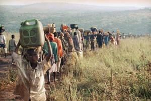 1994, Τανζανία.  Πρόσφυγες από τη Ρουάντα κουβαλάνε νερό στις σκηνές τους, στο στρατπόπεδο προσφύγων Μπενάκο, στην Τανζανία. Περισσότεροι από 250.000 άνθρωποι έχουν φύγει από τη Ρουάντα για να σωθούν από τη βία που μαστίζει τη χώρα.