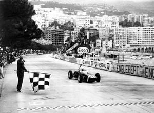 1961, Μόντε Κάρλο.  Ο Βρετανός οδηγός Στέρλινγκ Μος περνάει πρώτος τη γραμμή του τερματισμού στο Γκραν Πρι του Μονακό. Ο Μος οδηγεί μια Λότους.