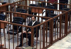 2006, Βαγδάτη.  Ο πρώην Πρόεδρος του Ιράκ, Σαντάμ Χουσεΐν, ακούει τις εναντίον του κατηγορίες, από τον πρόεδρο του δικαστηρίου, κατά τη διάρκεια της δίκης του στην Πράσινη Ζώνη στη Βαγδάτη. Ο Χουσεΐν κατηγορείται για δολοφονίες, βασανισμούς και παράνομες