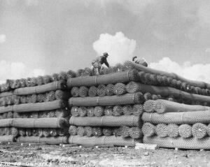 1944, Αγγλία.  Αμερικανοί στρατιώτες στιβάζουν τεράστιες ποσότητες συρματοπλέγματος, καθώς οι συμμαχικές δυνάμεις στην Αγγλία ετοιμάζονται πυρετωδώς για τη μεγάλη απόβαση στην ηπειρωτική Ευρώπη.
