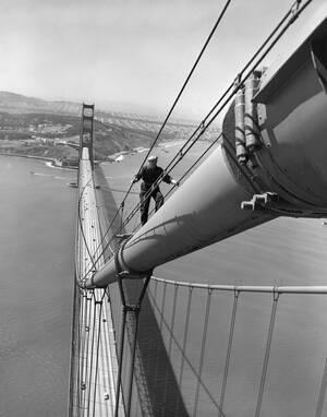 1952, Σαν Φρανσίσκο.  Ένας εργάτης συντήρησης, βρίσκεται σκαρφαλωμένος επάνω στη γέφυρα Γκόλντεν Γκέιτ στο Σαν Φρανσίσκο. Η γέφυρα χτίστηκε στο σημείο που συναντώνται ο Ειρηνικός Ωκεανός και η κόλπος του Σαν Φρανσίσκο.