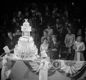 1962, Νέα Υόρκη. Ο Αμερικανός Πρόεδρος Τζον Φ. Κένεντι κοιτάει την τούρτα των γενεθλίων του, στο Μάντισον Σκουέαρ Γκάρντεν. Το Δημοκρατικό Κόμμα οργάνωσε το πάρτι γενεθλίων του Κένεντι, προκειμένου να συγκεντρώσει εισφορές. Τα γενέθλια του Κένεντι είναι σ