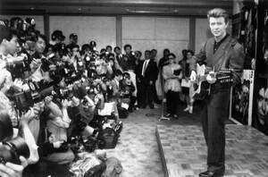 1990, Τόκιο. Ο Ντέιβιντ Μπάουι παίζει ακουστική κιθάρα κατά τη διάρκεια συνέντευξης Τύπου πριν ξεκινήσει την περιοδεία του στην Ιαπωνία.