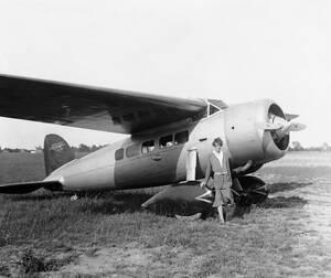 1932, Λόντοντέρι.  Η Αμέλια Έρχαρντ στέκεται δίπλα στο μονοπλάνο με το οποίο έγινε η πρώτη γυναίκα που διέσχισε χωρίς στάση τον Ατλαντικό Ωκεανό, ακολουθώντας τα βήματα του Λίντμπεργκ που έκανε το ίδιο λίγα χρόνια νωρίτερα.