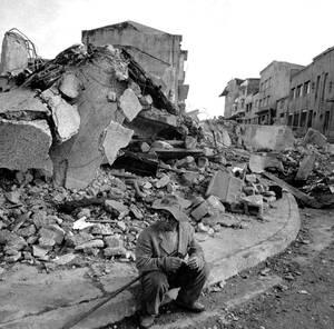 1960, Χιλή.  Ένας κάτοικος της πόλης Κάστρο, στη νότια Χιλή κάθεται στο πεζοδρόμιο σε αυτό που ήταν το κέντρο της πόλης, πριν το διαλύσει ο καταστροφικός σεισμός.