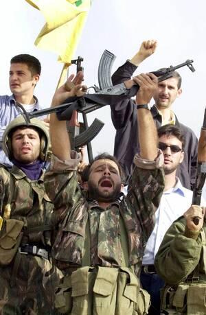 2000, Νότιος Λίβανος.  Λιβανέζοι μαχητές της Χεζμπολάχ φωνάζουν συνθήματα κατά του Ισραήλ, καθώς οι ισραηλινές δυνάμεις αποσύρονται. Το Ισραήλ κατείχε τα εδάφη του νοτίου Λιβάνου για περίπου δύο δεκαετίες.
