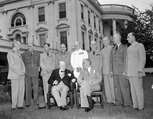 1943, Ουάσινγκτον.  Στον κήπο του Λευκού Οίκου, ο Βρετανός Πρωθυπουργός Ουίνστον Τσόρτσιλ και ο Πρόεδρος των ΗΠΑ Φρανκλίνος Ρούσβελτ, καθιστοί στο κέντρο, ενώ γύρω τους είναι οι επικεφαλής των σωμάτων στρατού, αεροπορίας και ναυτικού των δύο χωρών.
