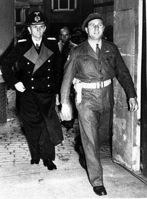 1945, Φλένσμπουργκ.  Ο επικεφαλής του Ναυτικού της Γερμανίας, Ναύαρχος Καρλ Ντένιτζ, συνοδεύεται από έναν Βρετανό αξιωματικό μετά τη σύλληψή του από τις βρετανικές δυνάμεις.