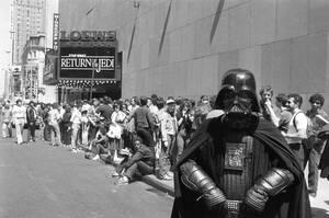 """1983, Νέα Υόρκη.  Ένας φανατικός του """"Star Wars"""", με τη στολή του Νταρθ Βέιντερ, ποζάρει μπροστά από έναν κινηματογράφο στην Τάιμς Σκουέαρ, όπου άλλοι φανατικοί κάνουν ουρά για την πρεμιέρα της ταινίας """"The Return of the Jedi"""", την τρίτη της σειράς."""