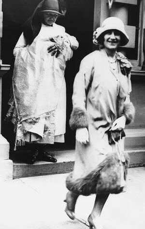 1926, Λονδίνο.  Μια νοσοκόμα κρατάει την πριγκίπισσα Ελισάβετ και ακολουθεί τη μητέρα του μωρού, Δούκισσα της Υόρκης, καθώς κατευθύνονται στη βάπτιση της Ελισάβετ.