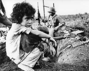 1965, Βιετνάμ.  Ένα κορίτσι του οποίου οι γονείς σκοτώθηκαν από δυνάμεις των Βιετκόνγκ στη μάχη του Dong Xoai, κάθεται με τα υπάρχοντά του στα ερείπια του χωριού της. Στο πίσω μέρος της φωτογραφίας, ένα Νοτιοβιετναμέζος στρατιώτης φυλάει την περίμετρο.