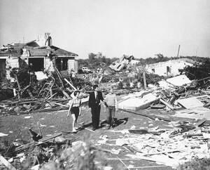 1953, Μασαχουσέτη.  Ο γερουσιαστής της πολιτείας της Μασαχουσέτης, Τζον Φ. Κένεντι, συνοδευόμενος από δύο 15χρονα παιδιά, περπατάει ανάμεσα στα ερείπια που άφησε πίσω του ο τυφώνας που χτύπησε την πολιτεία. Τουλάχιστον 86 άνθρωποι έχασαν τη ζωή τους, 800