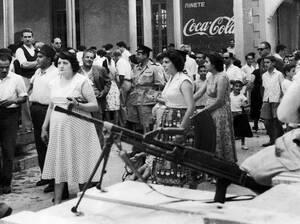 1958, Λευκωσία.  Στη σκιά ενός οπλοπολυβόλου, επανδρωμένου από ένα Βρετανό στρατιώτη, Ελληνοκύπριοι σπεύδουν να αγοράσουν τρόφιμα, στην οδό Λήδρας, στη Λευκωσία. Εκμεταλεύονται τη μια ώρα άρσης της απαγόρευσης κυκλοφρίας που επιβλήθηκε μετά από τα πρόσφα