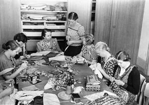 """1938, Βερολίνο.  Η έμφαση δίνεται στο σωστό χειρισμό της βελόνας στα μαθήματα που λαμβάνουν οι μελλοντικές σύζυγοι, στη """"σχολή για νύφες"""" του Schwanenwerder, μιας οργάνωσης των Ναζί για γυναίκες."""