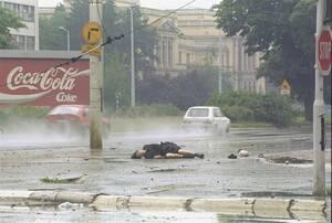 """1992, Σαράγιεβο.  Το νεκρό σώμα μιας γυναίκας βρίσκεται στη μέση του δρόμου στο Σαράγιεβο. Έχει χτυπηθεί από ελεύθερο σκοπευτή. Η συγκεκριμένη μέρα περιγράφηκε ως """"σχετικά ήσυχη, με σποραδικά πυρά""""."""
