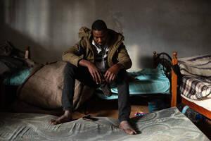Ο 17χρονος Χασάν, από το Νταρφούρ του Σουδάν, έφτασε στη Λιβύη πριν από ένα χρόνο. Συνελήφθη και κρατήθηκε σε κέντρα κράτησης. Έσπασε και τα δύο πόδια του, ενώ προσπαθούσε να δραπετεύσει από το κέντρο κράτησης Τατζούρα και λέει ότι χτυπήθηκε έντονα από το