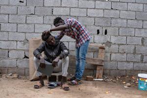 Πρόσφυγες κυρίως από το Νταρφούρ του Σουδάν συγκεντρώνονται στην αυλή στην περιοχή Γκόργκι, όπου ζουν, νότια της Τρίπολης. Οι μετανάστες και οι πρόσφυγες ζουν συχνά σε άθλιες συνθήκες, σε ερειπωμένα κτίρια ή μικρά ημιτελή σπίτια και στερούνται βασικών υπη