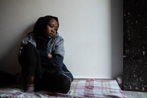 Η Λαία, η 13χρονη κόρη της Αβουάια, κάθεται σε ένα στρώμα στο πάτωμα. Μαζί με τη μητέρα και την αδελφή της  ζουν στη Λιβύη από το 2018 αφού εγκατέλειψαν τη χώρα τους, το Σουδάν, λόγω του πολέμου. Όταν έφθασαν στη Λιβύη  έπεσαν θύματα απαγωγής και κάποιοι