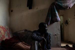 Ο Μπανάτζα, 35 ετών, κατάγεται από το Νταρφούρ του Σουδάν. Ζει στη Λιβύη τα τελευταία 10 χρόνια και δουλεύει σε εργοστάσιο ξυλείας. Λέει ότι ποτέ δεν σκέφτηκε να φύγει από τη Λιβύη επειδή αισθάνεται τυχερός που έχει δουλειά και ένα μικρό καταφύγιο για να