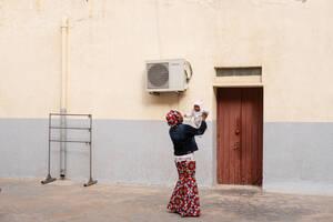 Μια γυναίκα από τη Νιγηρία παίζει έξω από την εκκλησία του Σαν Φράνσις στην Τρίπολη, με το μωρό της, που γεννήθηκε στη Λιβύη. Ζει στη χώρα εδώ και πάνω από 4 χρόνια, καθώς ο σύζυγός της βρήκε δουλειά. Παρά τη δύσκολη κατάσταση, προς το παρόν δεν σκέφτοντα