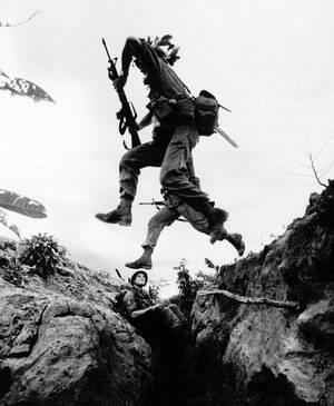 1965, Βιετνάμ.  Αμερικανοί πεζοναύτες πηδάνε πάνω από ένα χαράκωμα για να πάρουν τις θέσεις τους, στο αεροδρόμιο του Phouo Vinh. Αποστολή τους είναι να προστατεύσουν το αεροδρόμιο από πιθανή επίθεση των Βιέτ Κονγκ.
