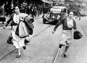1937, Μπιλμπάο.  Άνθρωποι τρέχουν να βρουν καταφύγιο από τις βόμβες, στο Μπιλμπάο, κατά τη διάρκεια αεροπορικής επιδρομής στον Ισπανικό Εμφύλιο πόλεμο.