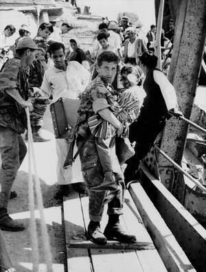 1967, Ιεριχώ.  Ένας Ισραηλινός στρατιώτης κρατάει ένα μικρό κορίτσι από αραβική οικογένεια, καθώς οι πρόσφυγες διασχίζουν τη γέφυρα Άλενμπι πάνω από τον ποταμό Ιορδάνη. Οι Αραβες φεύγουν κατά δεκάδες χιλιάδες από τη Δυτική Όχθη προς την Ιορδανία.