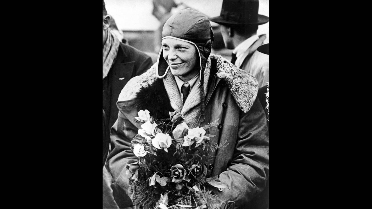 """1928, Σαουθάμπτον.  Η Αμερικανίδα αεροπόρος Εμίλια Έρχαρτ κρατάει μια ανθοδέσμη λίγο μετά την άφιξή της στο Σαουθάμπτον της Αγγλίας από το υπερατλαντικό της ταξίδι με το αεροσκάφος """"Friendship"""". Το τρικινητήριο """"Friendship"""" πιλοτάρισαν δύο άντρες, ενώ η"""