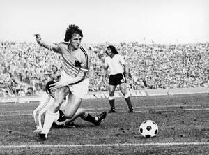 1974, Γκέλσενκίρχεν.  Ο παίκτης της εθνικής Ολλανδίας Γιόχαν Κρόιφ ετοιμάζεται να σουτάρει στα αντίπαλα δίχτυα, στο ματς ανάμεσα στην Ολλανδία και την Αργεντινή για το δεύτερο γύρο του Παγκοσμίου Κυπέλλου της Γερμανίας. Η Ολλανδία κέρδισε με 4-0.