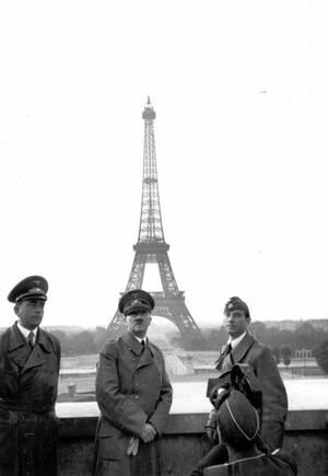 1940, Παρίσι.  Ο Αδόλφος Χίτλερ στο Παρίσι, ποζάρει με τον πύργο του Άιφελ πίσω του, μια μέρα μετά την επίσημη παράδοση της Γαλλίας. Δίπλα του, ο αρχιτέκτονας του Ράιχ, Άλμπερτ Σπέερ και ο Άρνο Μπρέκερ, αγαπημένος γλύπτης του Φίρερ.