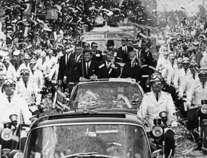 """1963, Βερολίνο.  Το Βερολίνο υποδέχεται τον Τζον Φ. Κένεντι, ο οποίος είναι καθ' οδόν για να δώσει την περίφημη """"είμαι ένας Βερολονέζος"""" (Ich bin ein Berliner) ομιλία του."""