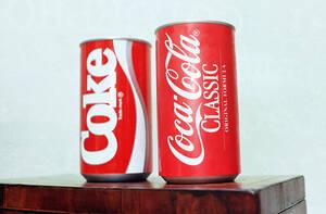 1985, Ατλάντα. Τα δύο κουτάκια του διάσημου αναψυκτικού, το ένα της  New Coke και το άλλο της Coca-Cola Classic εκτείθενται κατά τη διάρκεια συνέντευξης Τύπου. Η New Coke λανσαρίστηκε ως βελτιωμενη φόρμουλα της κλασικής συνταγής, αλλά υπήρξαν τόσες αντιδρ